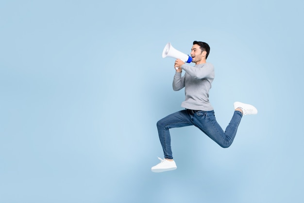 Young active man jumping and shouting on megaphone isolated  with copy space