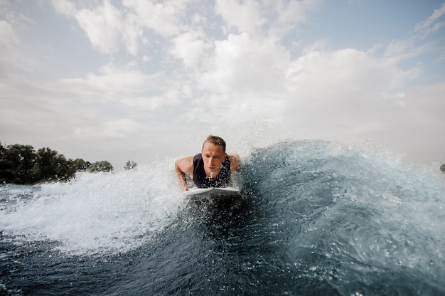 Young active man lying on the white wakeboard on the blue wave