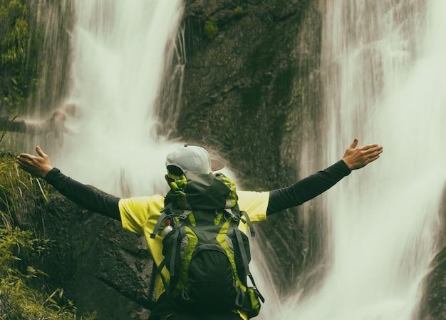 Молодой активный человек, поднимающий руки на фоне водопада. человек с рюкзаком и кепкой в походе