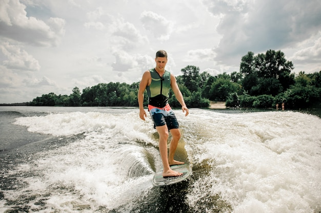 Young active man wakesurfing on the board down the river against the cloudy sky and trees