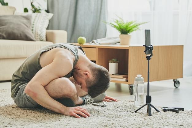 Молодой активный мужчина со скрещенными ногами сидит на полу в гостиной и наклоняется вперед во время утренней тренировки на карантине