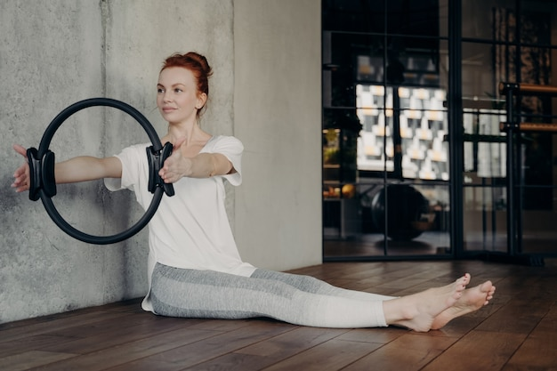 Young active red haired lady sitting with legs stretched forward and holding pilates ring by both hands performing strength exercises in fitness studio or gym. concept of healthy lifestyle and sport