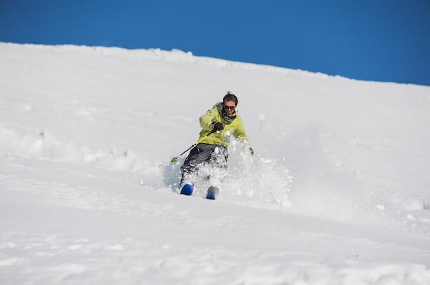 Молодой активный лыжник в ярко-желтой спортивной одежде катается по горам
