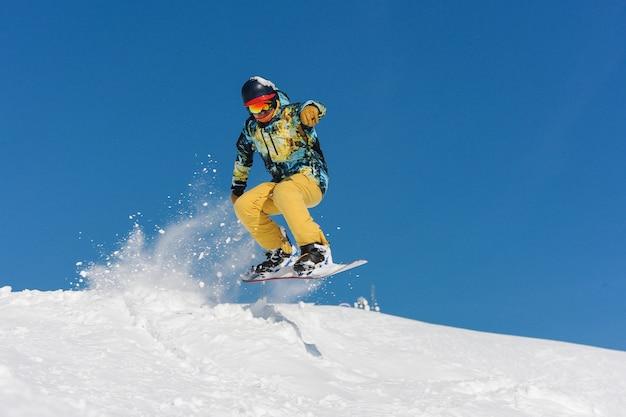 Молодой активный сноубордист в яркой спортивной одежде прыгает на склоне горы