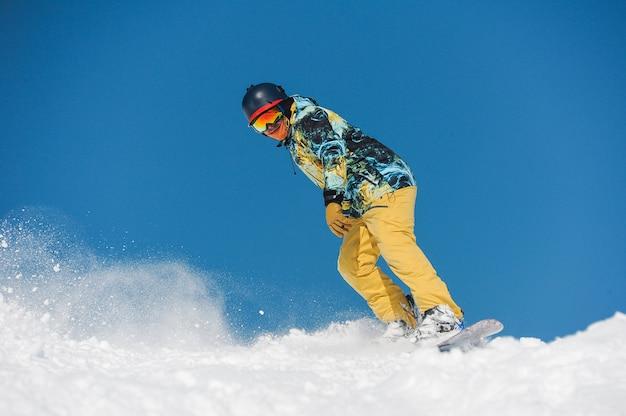 山の斜面を下って乗って明るいスポーツウェアの若いアクティブなスノーボーダー