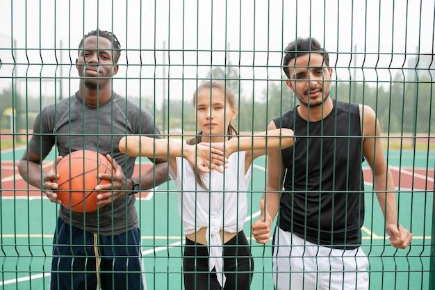 ゲームの合間に休憩しながらバスケットボールネットで立っているスポーツウェアの若いアクティブな女性と2人の男性