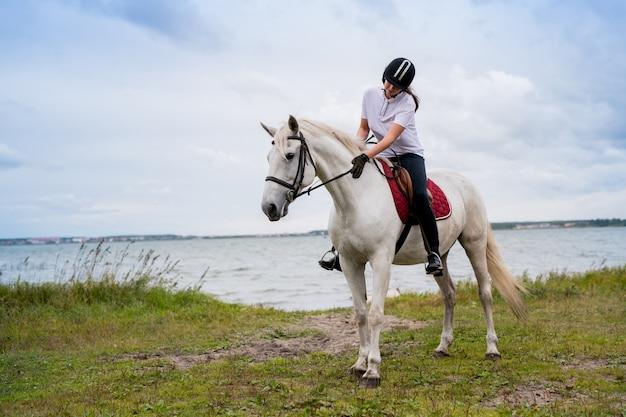 訓練中に白い競走馬の背中に座っている間川沿いに移動する馬術の服装の若いアクティブな女性