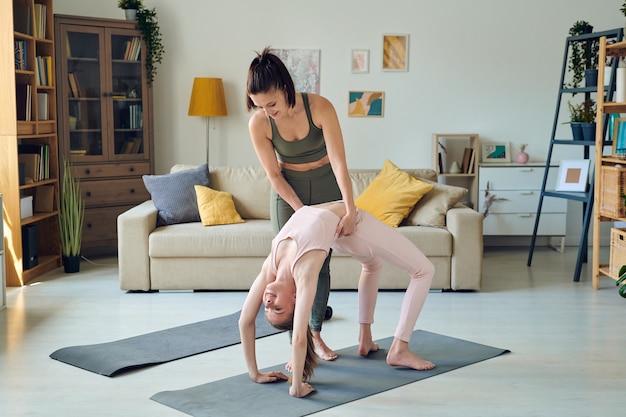 가정 환경에서 매트에서 백벤드 운동을 하는 동안 분홍색 운동복을 입은 10대 딸을 돕는 회색 운동복을 입은 젊은 활동적인 여성