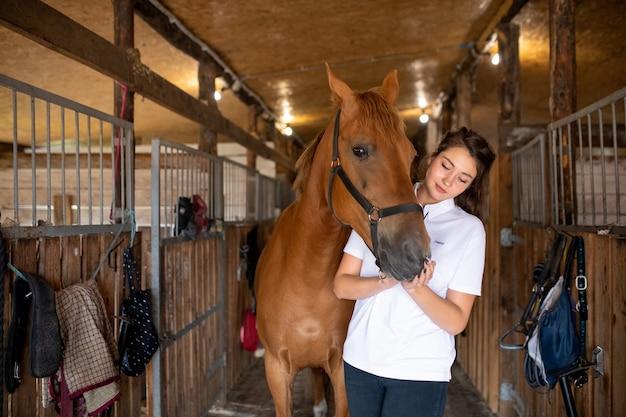 茶色の純血種の競走馬によって馬小屋の中に立って、彼女の鼻に触れる白いシャツの若いアクティブな女性