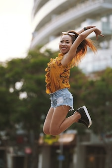 Young active woman performing a high jump in the street
