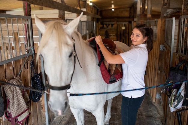 レースやトレーニングの準備中に白い純血種の競走馬の後ろにサドルを置く若いアクティブな女性