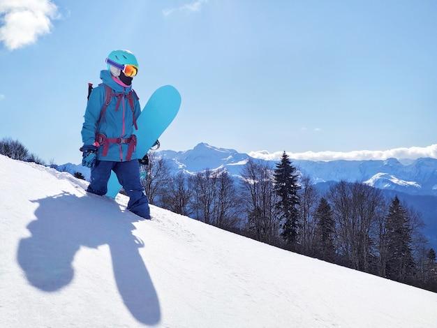 파노라마 산 배경에서 가루 눈에 스노우 보드와 함께 서있는 젊은 활성 여자