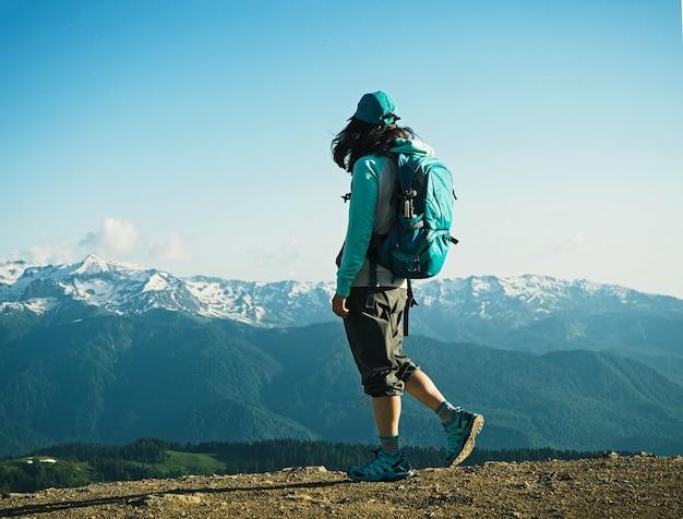 山の背景で歩く若いアクティブな女性