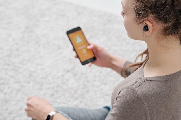 ヨガの練習中に足を組んで床に座っている間スマートフォンを保持しているエアポッドを持つ若いアクティブな女性