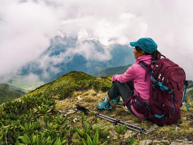 座って、リラックスして山の背景を見てバックパックを持つ若いアクティブな女性