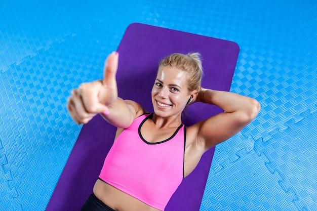 フィットネスクラスで腹部のクランチがヨガマットで運動した後、リラックスしたスリムな体を持つ若いアクティブな女性。スポーティな人々、健康的なライフスタイル