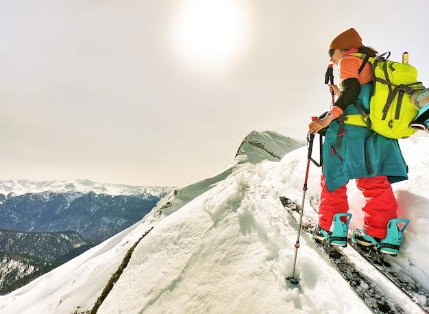 산에서 스플릿 보드 스키 여행에 트레킹 폴을 가진 젊은 활성 여자