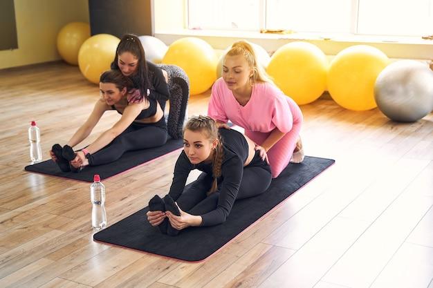 ヨガマットで体の柔軟性を保つためにストレッチ運動をしているスリムな体の若いアクティブな女性