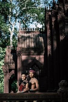 Giovane attore e attrice che indossa bellissimi costumi antichi, in monumenti antichi, in stile drammatico. esibisciti in una leggenda popolare storia d'amore, racconto popolare thai isan chiamato