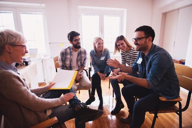 Молодые зависимые люди любят проводить время вместе на специальной групповой терапии. красивый радостный парень говорить шутки и высмеивать.