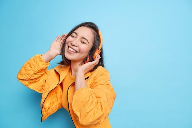 젊은 사랑스러운 아시아 여자는 눈을 감고 미소를 광범위하게 유지하고 헤드폰을 통해 음악을 듣고 파란색 벽에 세련된 옷 모델을 입은 좋아하는 노래를 즐긴다