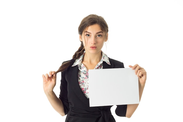 Young adorable brunette business woman in uniform with white placard in hands isolated on white wall