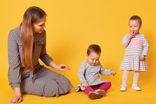 Young adorable caring mother looks after her little kids, sitting on floor with one of twin girls. sweet child puts one hand on her mouth