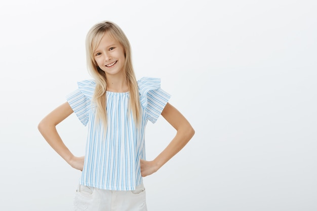 Young adorable daughter wants to help mom on kitchen. indoor shot of confident fashionable young girl with fair hair, holding hands on hips with self-assured smile, standing over gray wall