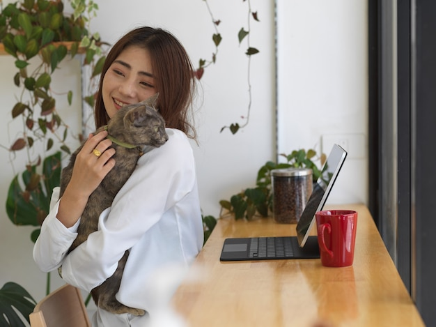 Young adorable female hugging her cat while working at home
