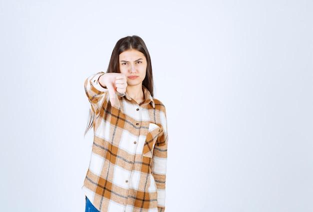 Giovane ragazza adorabile in abbigliamento casual che dà i pollici giù sulla parete bianca.