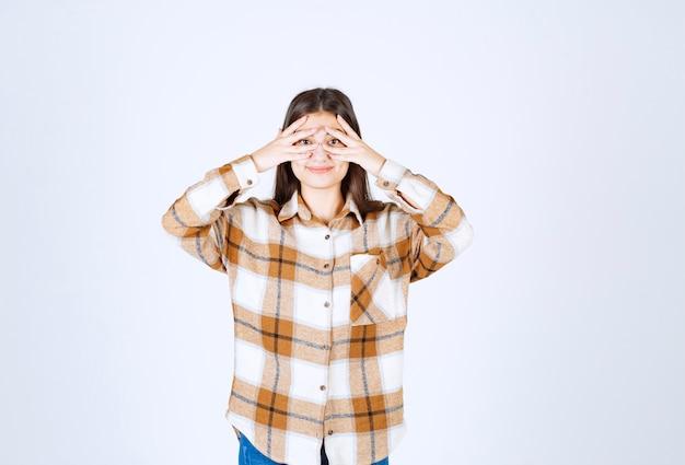 白い壁の上のカメラにポーズをとってカジュアルな服装で若い愛らしい女の子。