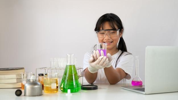 安全メガネと化学のためのフラスコを保持している手袋の愛らしい少女。