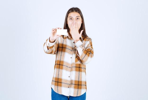 명함을 보여주고 흰 벽에 입을 가리고 있는 사랑스러운 어린 소녀.