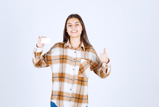 名刺を表示し、白い壁に親指をあきらめる若い愛らしい女の子。