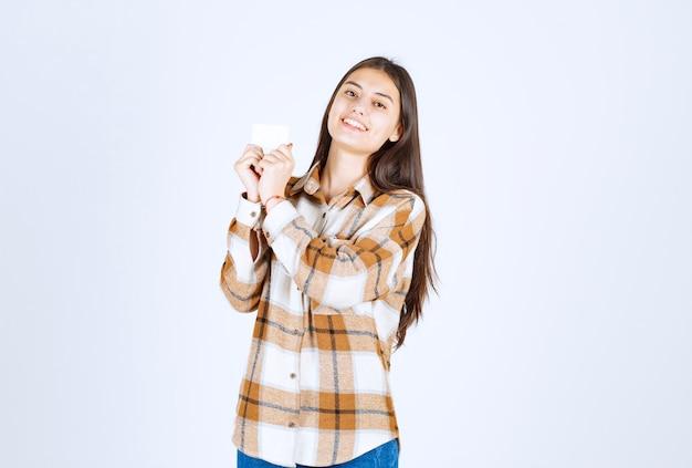 Giovane ragazza adorabile che mostra biglietto da visita sulla parete bianca.