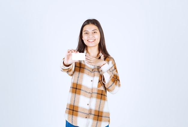 白い壁に幸せな気持ちの名刺を持つ若い愛らしい女の子。