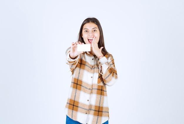 Giovane ragazza adorabile con il biglietto da visita che si sente felice sulla parete bianca.