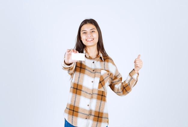 Giovane ragazza adorabile con il biglietto da visita che dà i pollici su sulla parete bianca.