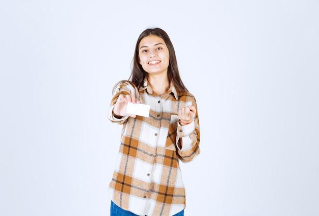 Giovane ragazza adorabile con biglietto da visita in piedi sul muro bianco.