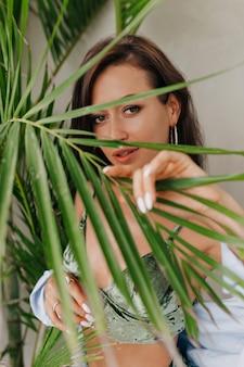 ヤシの葉で覆われ、流行のトップとシャツを着てカメラでポーズをとる大きな美しい目を持つ若い愛らしい女性テキストの場所