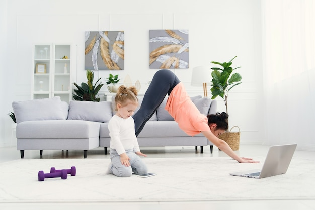 Young adorable mom makes stretching exercises and practicing yoga with baby girl at home. health