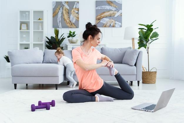 Молодая очаровательная мама делает упражнения на растяжку и занимается йогой с девочкой дома. концепция здравоохранения и спорта.