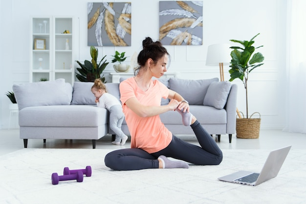 Young adorable mom making stretching exercises and practicing yoga with baby girl at home. healthcare and sports concept.