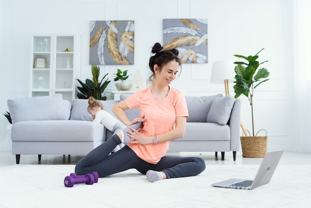 Young adorable mom making stretching exercises and practicing yoga with baby girl at home