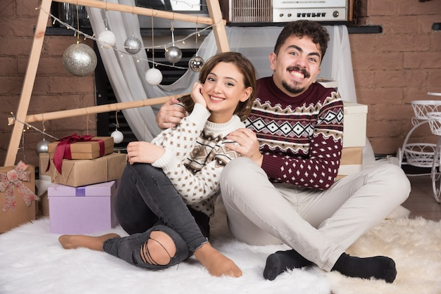 Young adorable smiling couple sitting on the floor and posing.