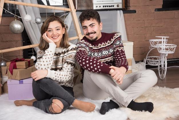 床に座ってポーズをとって若い愛らしい笑顔のカップル。