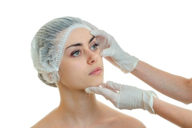 Молодая очаровательная женщина у пластического хирурга изолирована на белой стене
