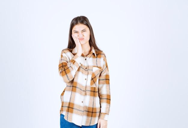 白い壁に歯痛があるカジュアルな服装の若い愛らしい女性。