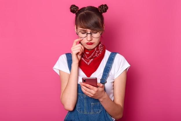 若い愛らしい女性がデニムのオーバーオール、カジュアルな白いtシャツ、首に赤いバンダナ、丸みを帯びた眼鏡を着て、ピンクで分離された彼女の携帯電話でsmsを読んでいる間、束は悲しく感じます