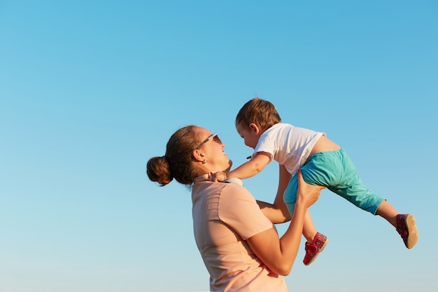 Young adorable woman with hair bun wearing casual t shirt holding toddler, having time with her daughter, little girl flying in sky in mommy's hands, against clear blue sky.